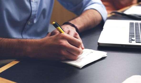 Homme qui écrit sur une feuille