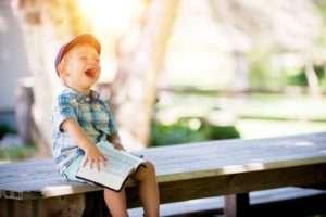 Sourire d'un enfant sur un banc un livre à la main