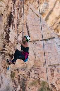 Jeune femme escaladant un rocher