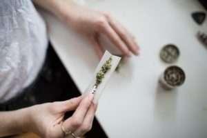Femme préparant une cigarette avec de la drogue