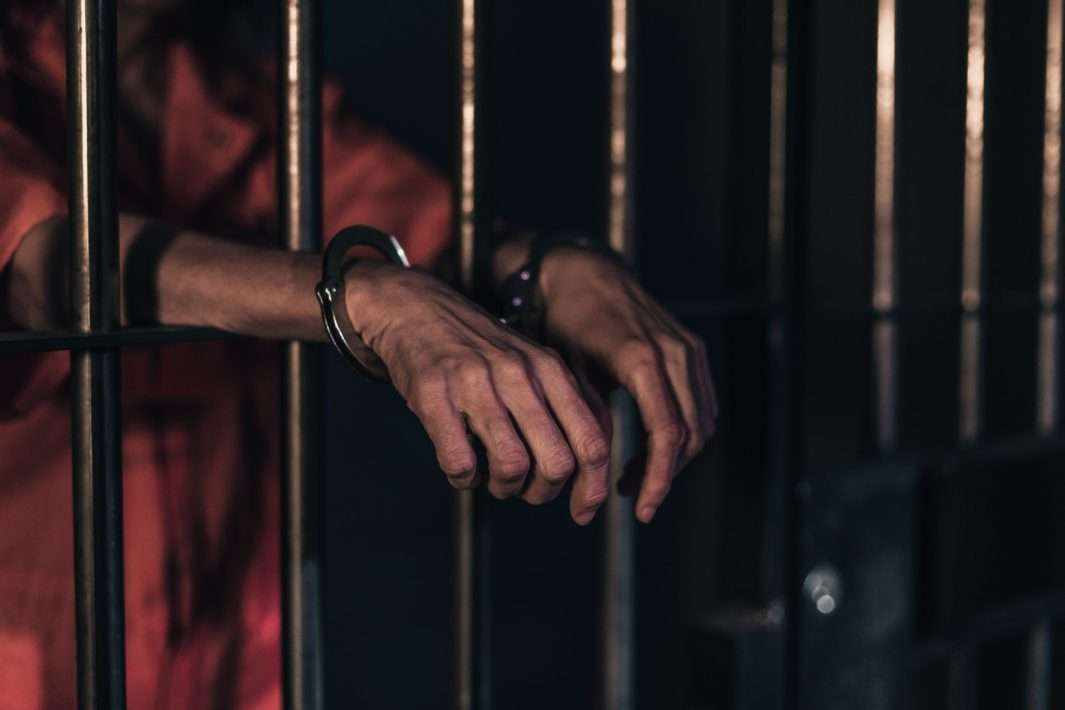 Homme menotté derrière les barreaux