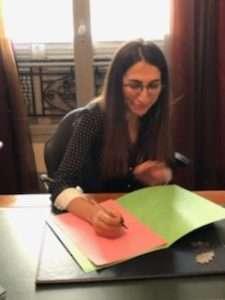 Emilie Bender en train de signer des documents