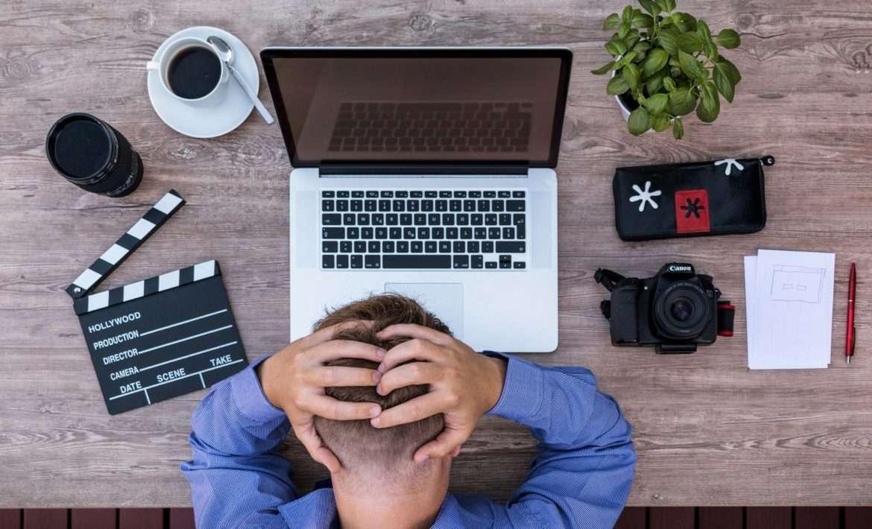 Homme se tenant le crâne devant un ordinateur
