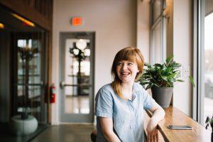 Femme trentenaire souriante près d'une fenêtre