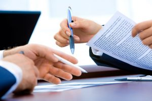 Deux personnes signant des papiers, le stylo à la main