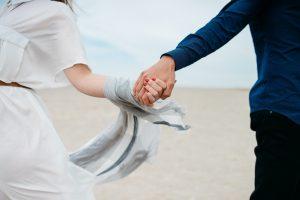 Un couple se tenant la main au bord de la plage
