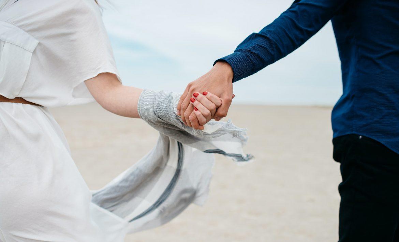Un couple se tenant la main sur la plage