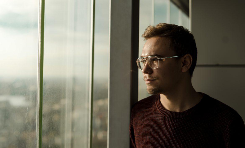 Homme trentenaire regardant par la vitre